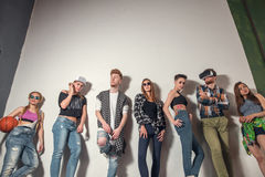 Studio portrait of seven young fashion attractive smiling caucasian women and men friends dressed jeans group together. Group of best friends having fun and stock image