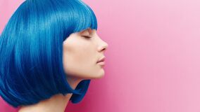 Portrait of a beautiful girl on a pink background. Girl with blue hair
