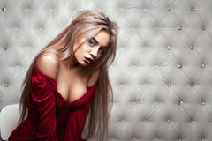 Studio portrait of a sexy blond in red dress. Over leather upholstery background. Elegant luxury woman with a seductive neckline and bare shoulders looks into Stock Photos