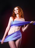 Studio portrait of young ginger woman covered in cloth Royalty Free Stock Photography