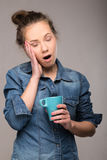 Studio portrait of a sleepy woman with a cup Royalty Free Stock Images