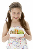 Studio Portrait of Smiling Girl Holding Lunchbox Stock Images