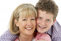 Studio Portrait of Smiling Teenage Boy with Mum Royalty Free Stock Image
