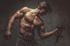 Portrait of sporty shirtless male with dumbbell. Studio portrait of sporty shirtless male with dumbbell on grey background Royalty Free Stock Image