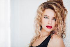 Sensual model with wavy blonde hair and red lips looking at camera against white background.