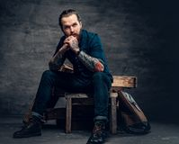 Bearded male with tattoos on arms. Studio portrait of stylish bearded male with tattoos on arms, sits on wooden boxes over grey background in a studio Stock Images