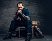 Bearded male with tattoos on arms. Studio portrait of stylish bearded male with tattoos on arms, sits on wooden boxes over grey background in a studio Royalty Free Stock Image