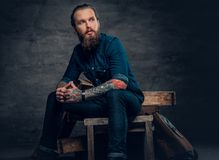 Bearded male with tattoos on arms. Studio portrait of stylish bearded male with tattoos on arms, sits on wooden boxes over grey background in a studio Royalty Free Stock Photos
