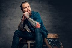 Bearded male with tattoos on arms. Studio portrait of stylish bearded male with tattoos on arms, sits on wooden boxes over grey background in a studio Royalty Free Stock Images