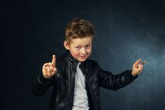Portrait of a boy in rock and roll style on a dark background royalty free stock photo
