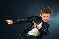 Portrait of a boy in rock and roll style on a dark background stock images