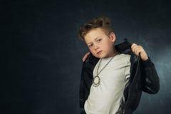 Studio portrait of a stylish boy in a leather jacket . Little rocker royalty free stock image