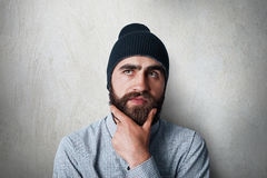 A studio portrait of stylish man with thick black beard wearing black cap and casual checked shirt having thoughtful look touching. His beard thinking about Royalty Free Stock Photos