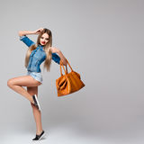 Studio portrait of a stylish square women denim dress with long blond hair, red lips, long legs,leather bag in hand Stock Images