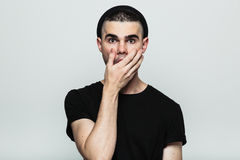 Studio portrait of suprised man. Studio portrait of suprised emotional young man with hand on face. Front view Royalty Free Stock Photography
