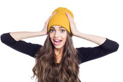 Portrait of surprised young woman wearing yellow beanie hat stock photography