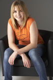 Studio Portrait Of Teenage Girl Sitting In Chair Stock Photos