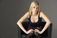 Studio Portrait Of Teenage Girl Sitting In Chair Royalty Free Stock Photography