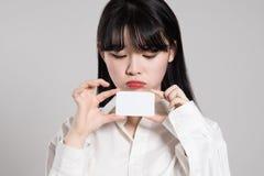 Studio portrait of twenties Asian woman enjoying having a card Royalty Free Stock Images