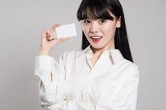 Studio portrait of twenties Asian woman enjoying having a card Royalty Free Stock Photography