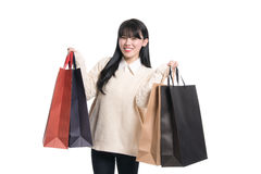 Studio portrait of twenties Asian woman happily shopping Royalty Free Stock Images