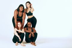 Multiracial females with different size and ethnicity stand together and smile. stock photo