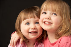 Studio Portrait Of Two Sisters Stock Photo