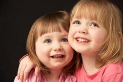 Studio Portrait Of Two Sisters Stock Photo