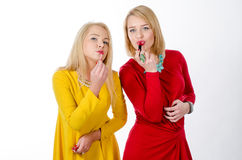 Studio portrait of two women with lipsticks Stock Image