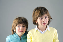 Studio portrait of two young brothers feeling worried royalty free stock image