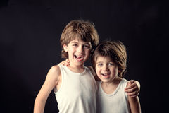 Studio portrait of two young brothers hugging and smiling Royalty Free Stock Image