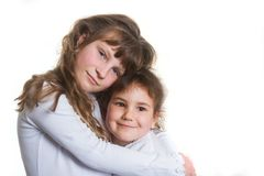 Studio portrait of two young happy smiling girls, sisters, over Stock Photo