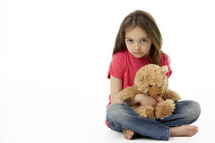 Studio Portrait Of Unhappy Girl with Teddy Bear. Sat Crossed Legged Stock Photography