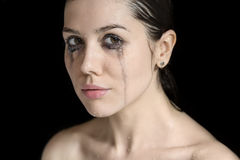 Studio portrait of wet woman. Beautiful wet girl looks into the camera on the black background in the studio. On her face there are flows of mascara and water Stock Photos