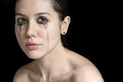 Studio portrait of wet woman. Cute wet girl looks into the camera on the black background in the studio. On her face there are flows of mascara and water drops Stock Images