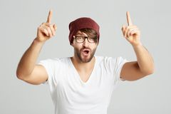 Handsome young man posing at studio. Studio portrait of a young bearded hipster man cheering with his arms raised in the air screaming and shouting on grey Stock Image