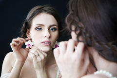 Studio portrait of a young beautiful bride looking in the mirror in a white dress. Professional make-up and hairstyle Stock Photo