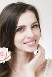 Studio portrait of a young beautiful bride. Professional make-up and hairstyle with flowers Royalty Free Stock Photography