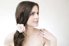 Studio portrait of a young beautiful bride. Professional make-up and hairstyle with flowers Royalty Free Stock Image
