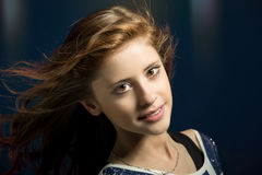 Studio portrait of young beautiful girl. Studio fashion portrait of young beautiful girl with nice eyes on dark blue background with wind from fan in hair Royalty Free Stock Photo