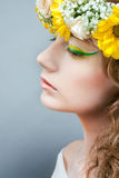 Studio portrait of young beautiful woman with flow. Studio portrait of young beautiful woman with yellow flowers in hair royalty free stock images