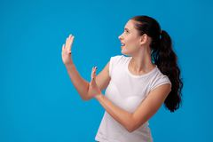 Studio portrait of a young beautiful woman in a white t-shirt against a blue wall background. People sincere emotions. Studio portrait of an exhausted woman in stock image
