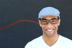 Studio portrait of young black man casual v-neck style wearing vintage glasses and hat isolated against dark background stock photo