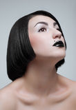 Studio portrait of young brunette with black lips. Studio portrait of young woman with black lips royalty free stock images