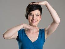 Studio portrait of young brunette cutie framing hands Stock Images