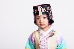 A studio portrait of a young girl wearing a Korean traditional costume, Hanbok, with a happy smile. Shot Stock Image