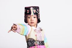A studio portrait of a young girl wearing a Korean traditional costume, Hanbok, pointing at something with a finger Royalty Free Stock Photos