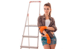 Studio portrait of young lovely girl in uniform makes renavation on ladder looking at the camera isolated on white Stock Photos