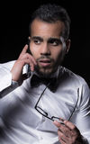 Studio portrait of young man. Portrait of man in white shirt talking by the phone Royalty Free Stock Image