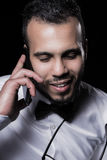 Studio portrait of young man. Portrait of man in white shirt talking by the phone Royalty Free Stock Photos
